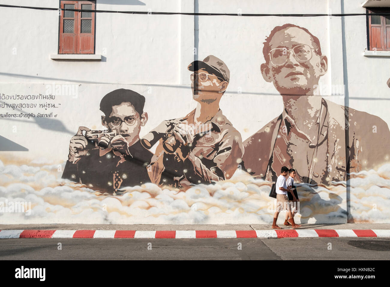 Thai schoolboys in Phuket Old Town pass a mural in remembrance of King Bhumibol Adulyadej.  As Thailand mourn the - Stock Image