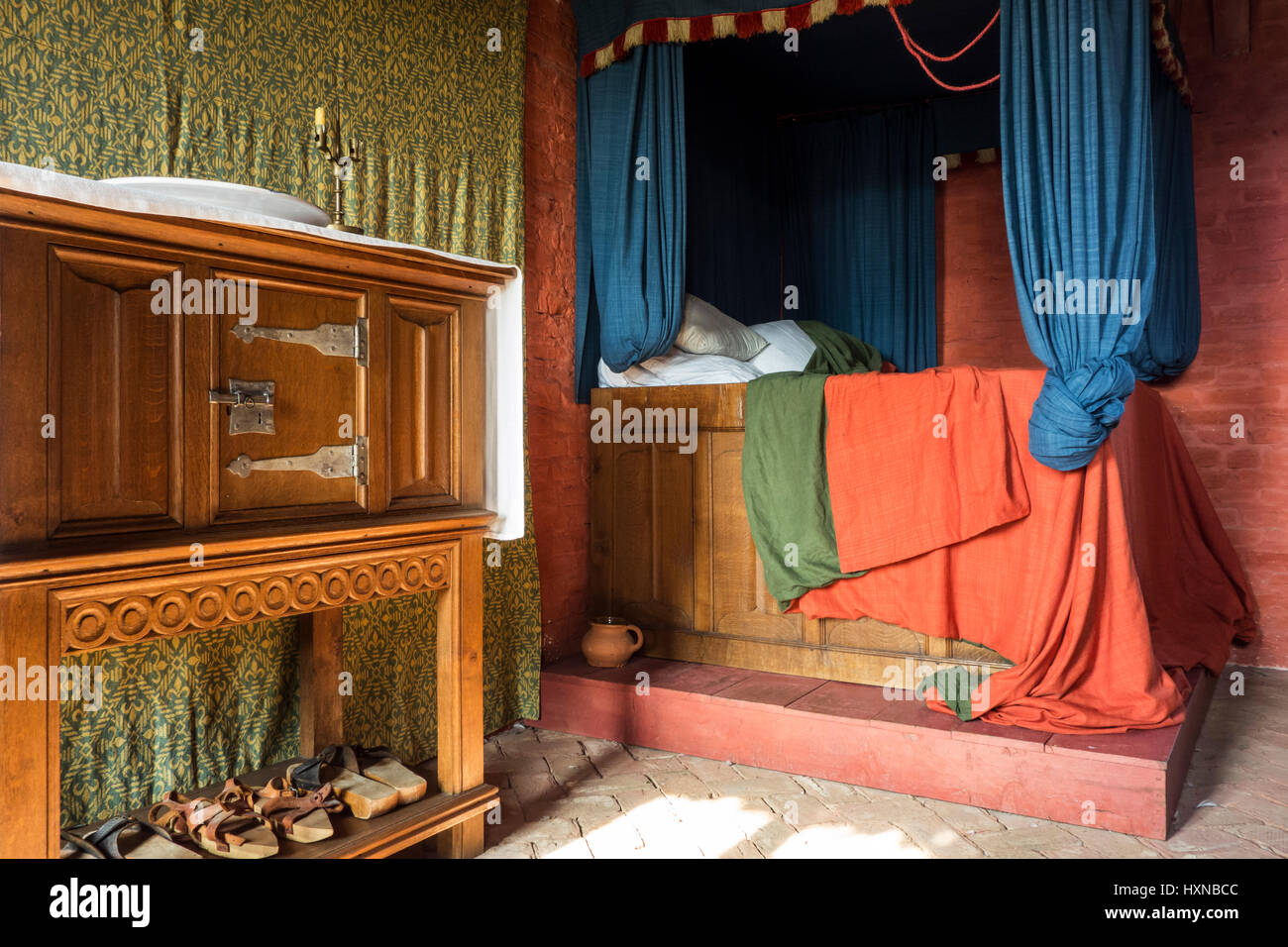 Colourful medieval curtained bedstead / bed with curtains in bedroom from the Middle Ages - Stock Image