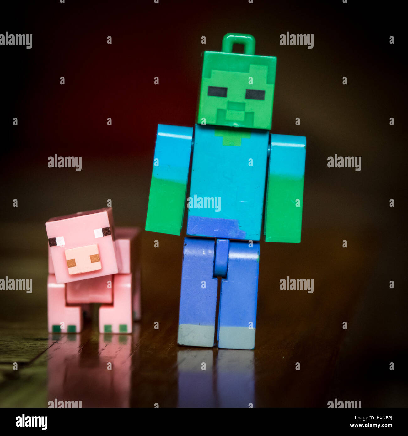 Minecraft pig with Steve standing on a coffee table in colour with window light - Stock Image