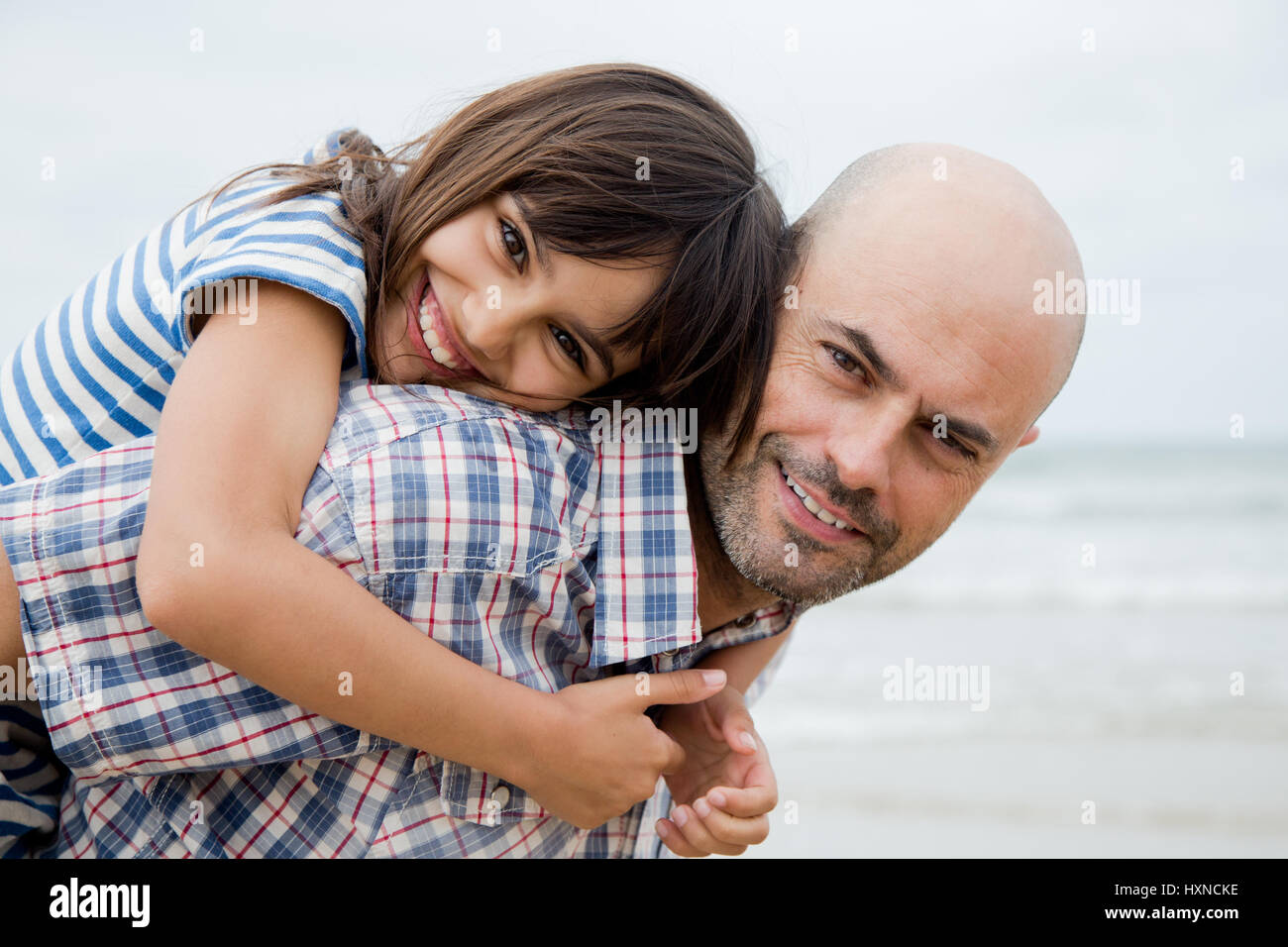 Father giving his daughter a piggy back ride on the beach in a cloudy day - Stock Image