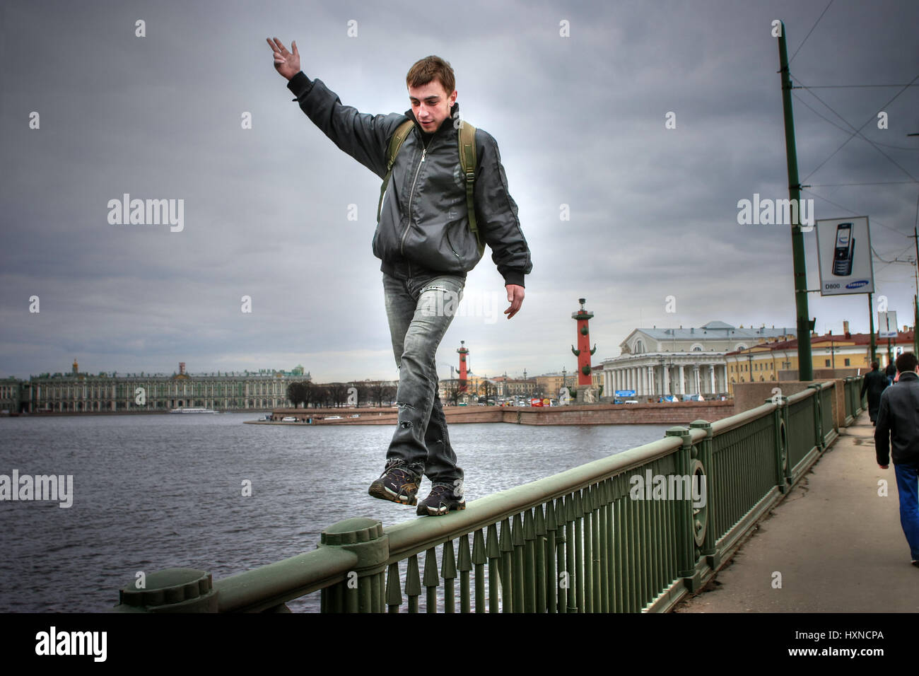 St. Petersburg, Russia - April 22, 2006: Young man is walking on thin parapet high bridge. - Stock Image
