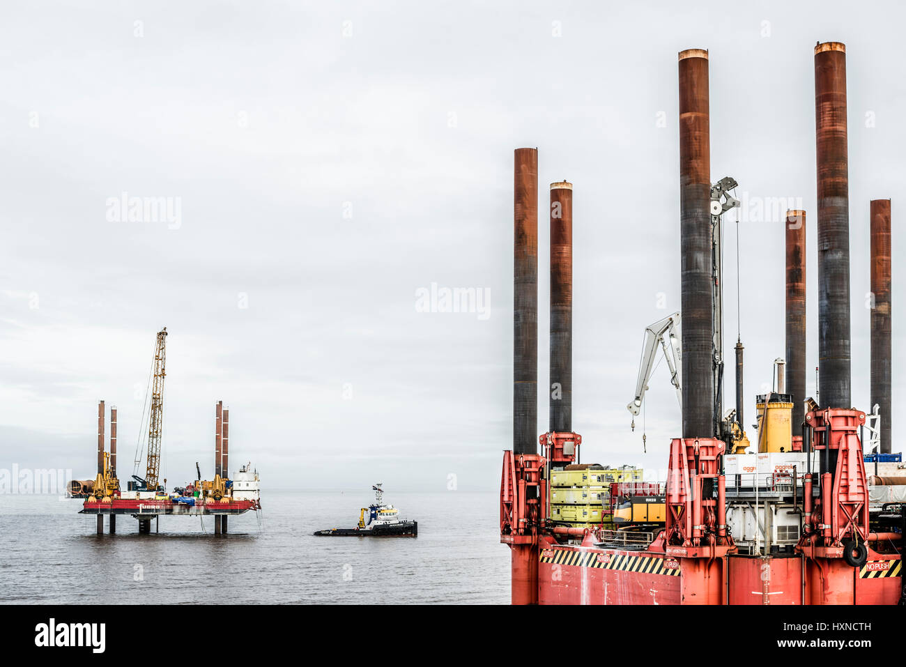 Offshore rigs and boat in the Bristol channel,druring the construction of Hinhley C power station. - Stock Image