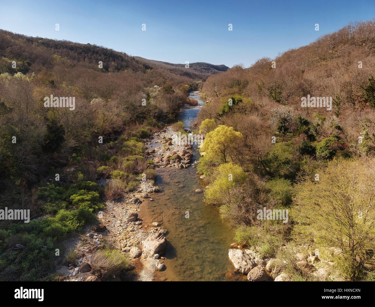 Small river on rocky ground, makes its way through the vegetation at the foot of the hill - Stock Image