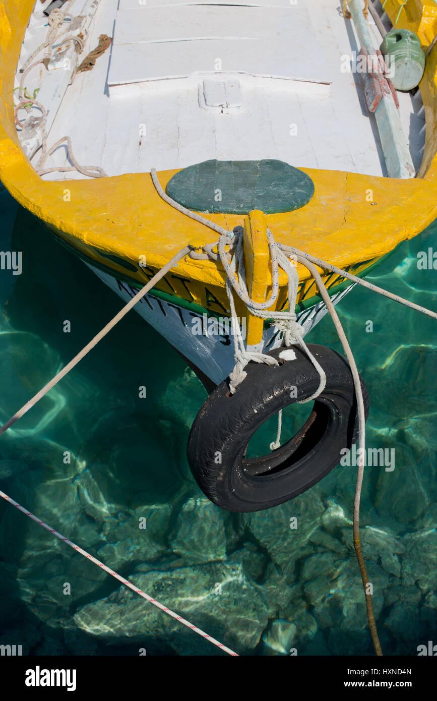 Detail von weiß-gelben Fischerboot auf grünem Wasser im Hafen von Iraklia Insel, kleine Kykladen, Griechenland - Stock Image