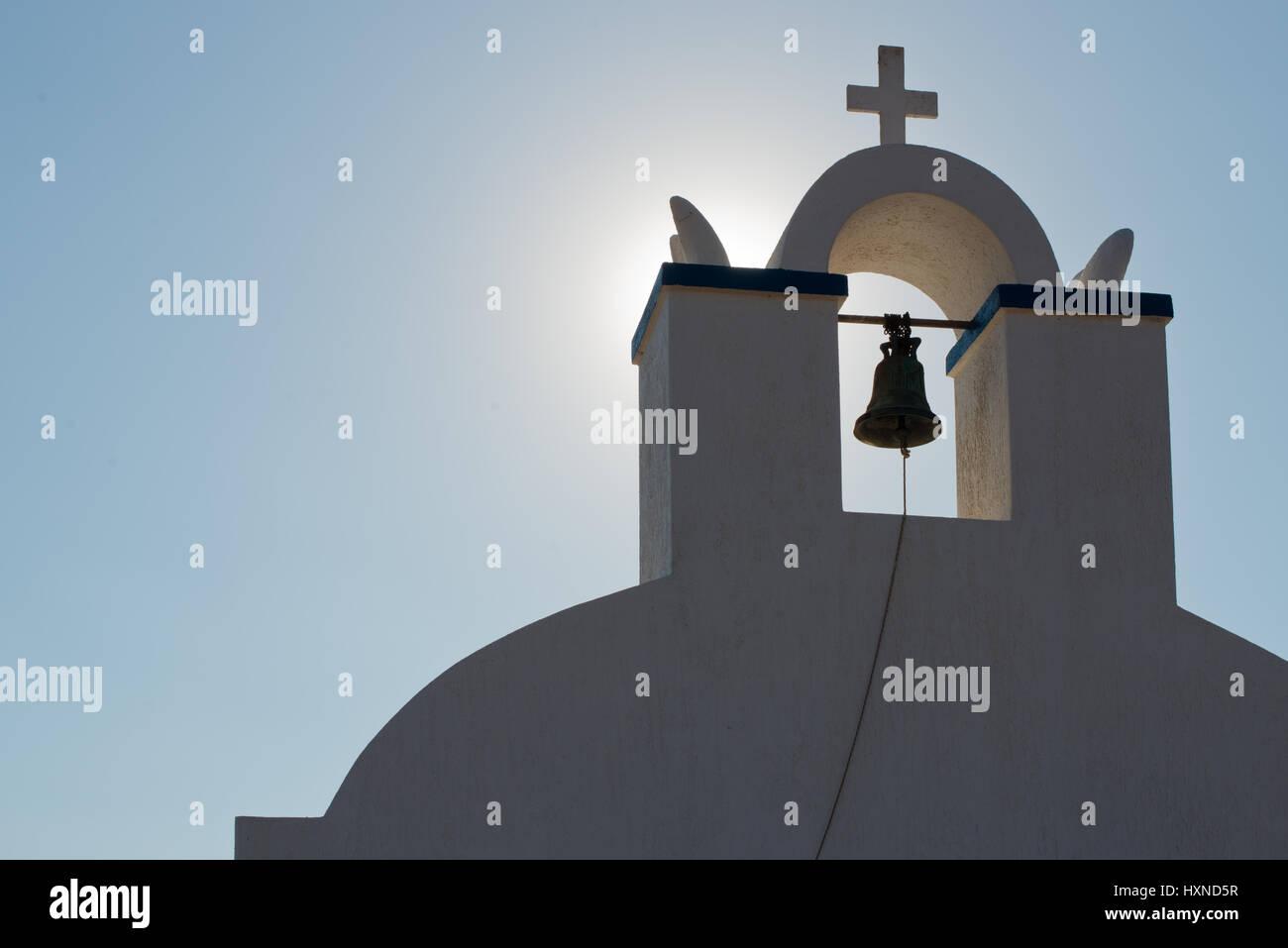 Glockenturm und Glocke einer Kapelle im Gegenlicht, Iraklia Insel, kleine Kykladen, Griechenland - Stock Image