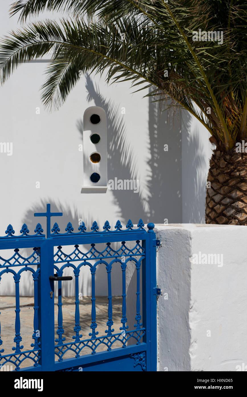 weiße Kirche mit blauem Eisentor und Palme auf Iraklia Insel, kleine Kykladen, Griechenland - Stock Image