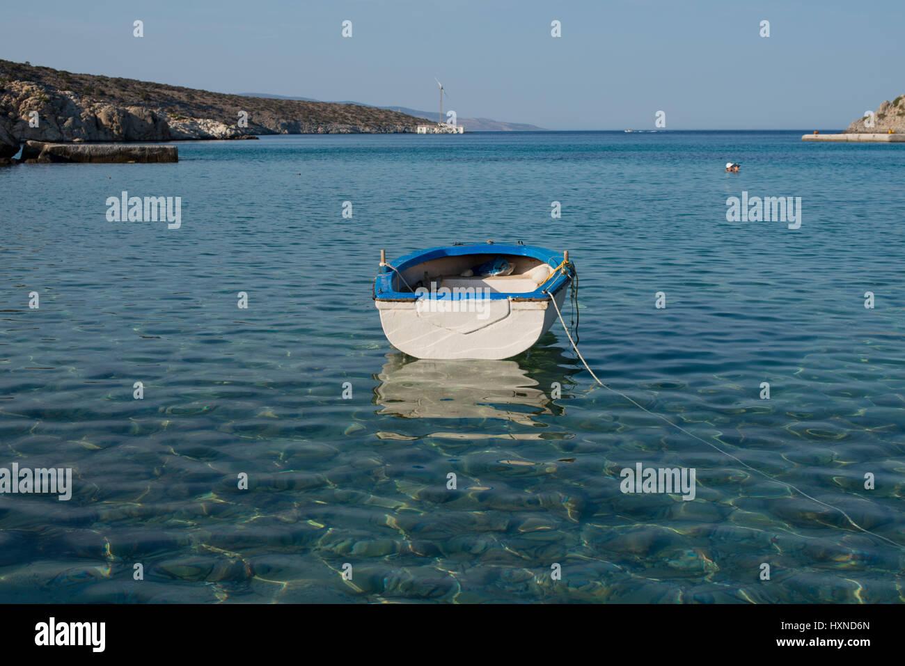 weiß-blaues kleines Boot vor Agios Georgios im gldenen Nachmittagslicht, Iraklia Insel, kleine Kykladen, Griechenland - Stock Image
