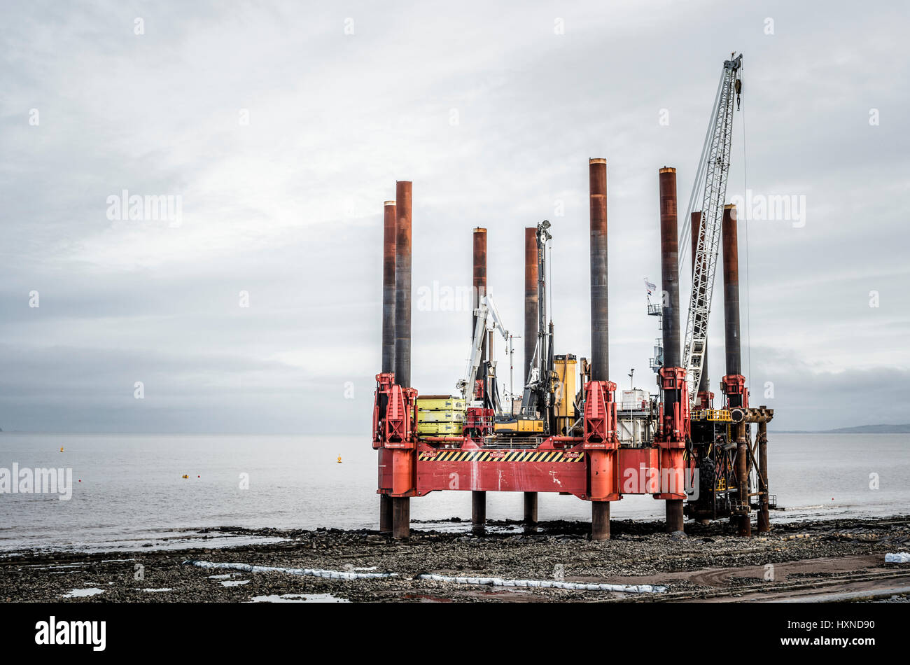 Offshore rigs at low tide on the Bristol channel,druring the construction of Hinhley C power station. - Stock Image