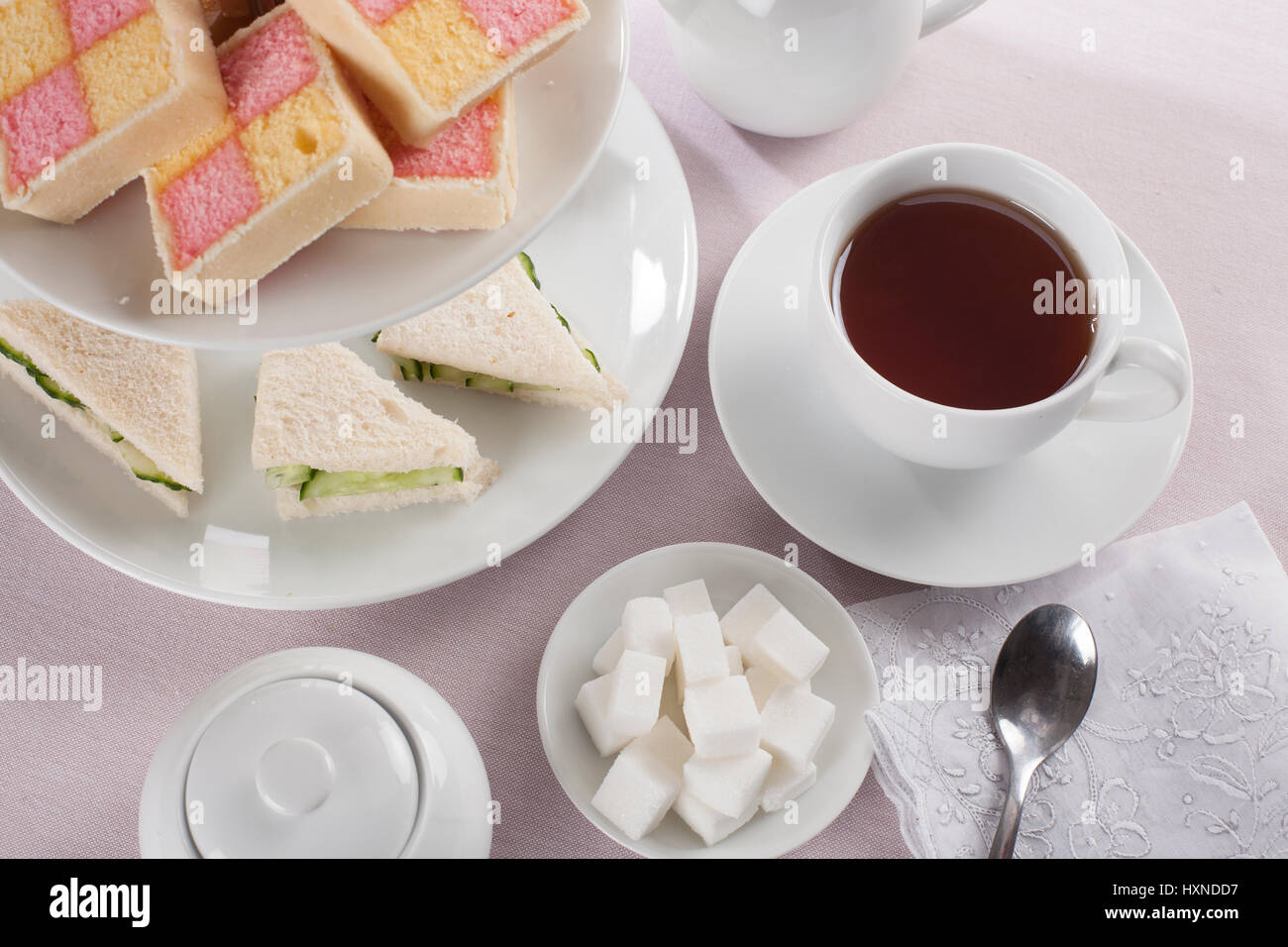 Tea with sugar cubes and English teatime snacks of cucumber sandwiches and battenburg cakes - Stock Image