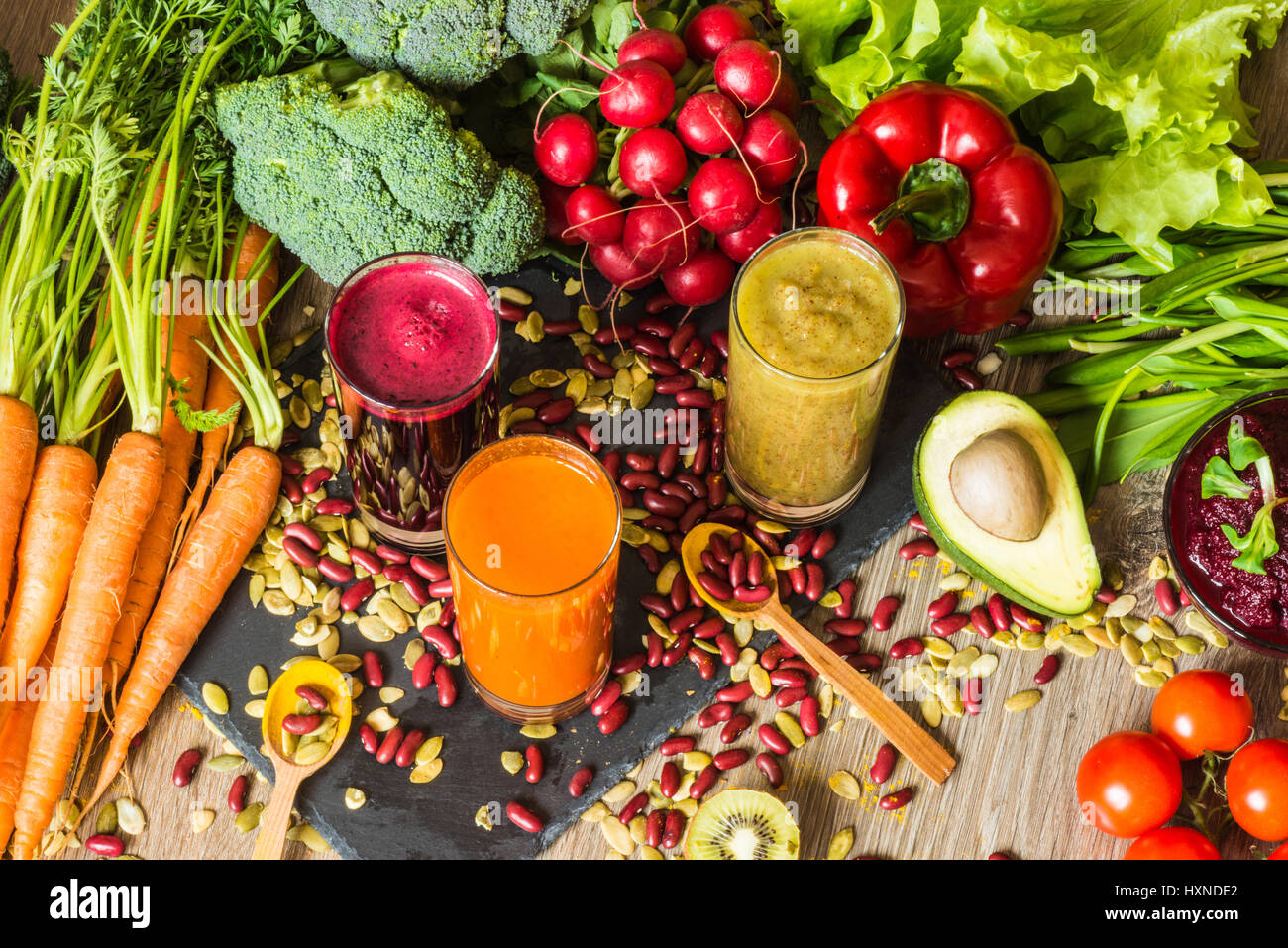 Healthy vegan food. Fresh vegetables on wooden background. Detox diet. Different colorful fresh juices - Stock Image