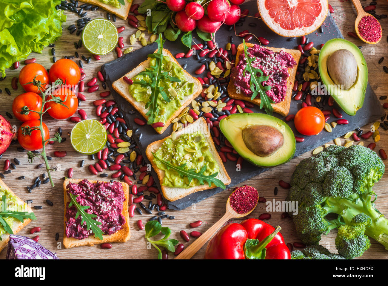 Healthy vegan food. Sandwiches and fresh vegetables on wooden background. Detox diet. Different colorful fresh juices. - Stock Image