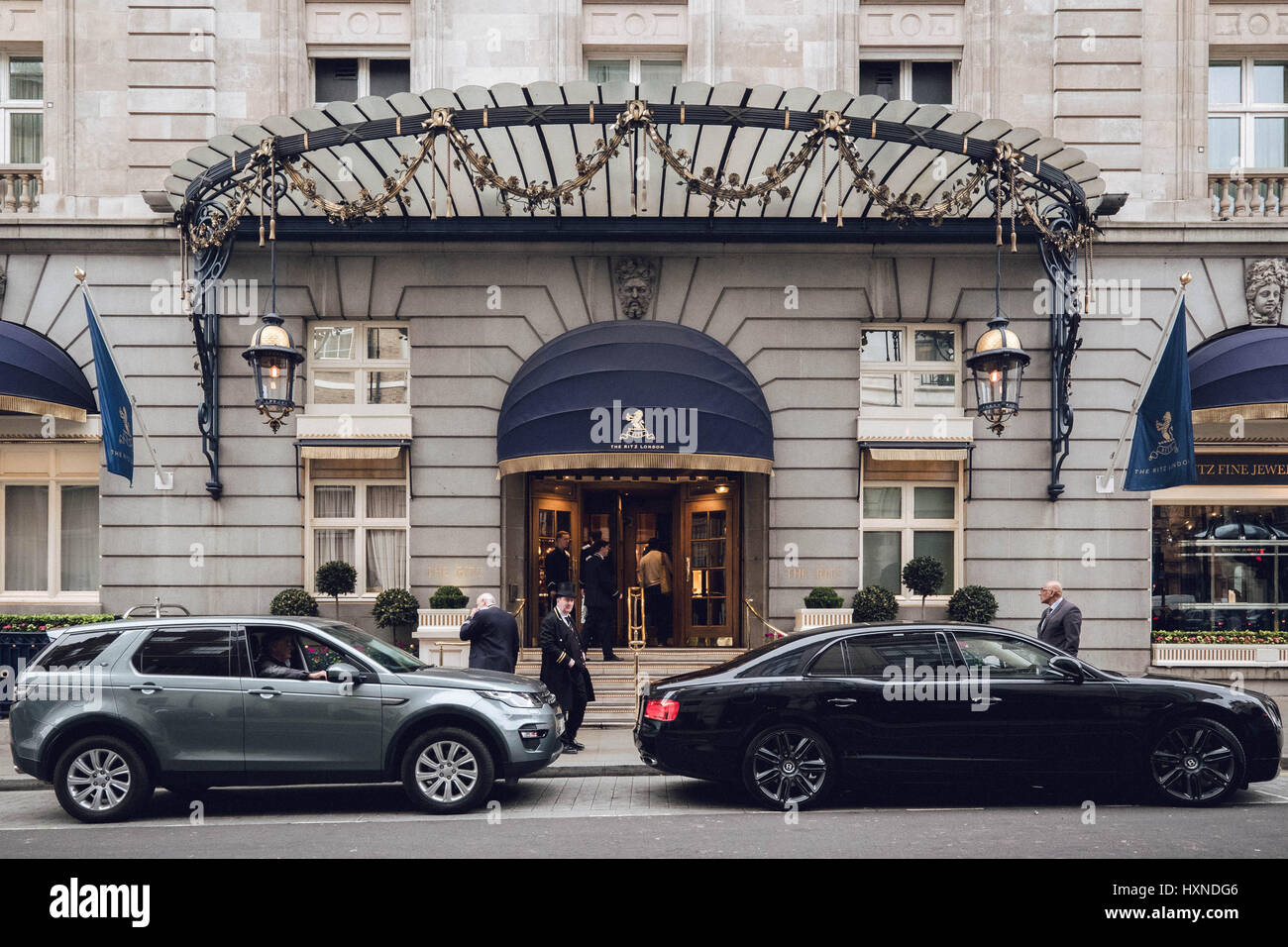 Colour photograph of the side entrance to London's The Ritz Hotel showing doormen and cars parked outside. - Stock Image