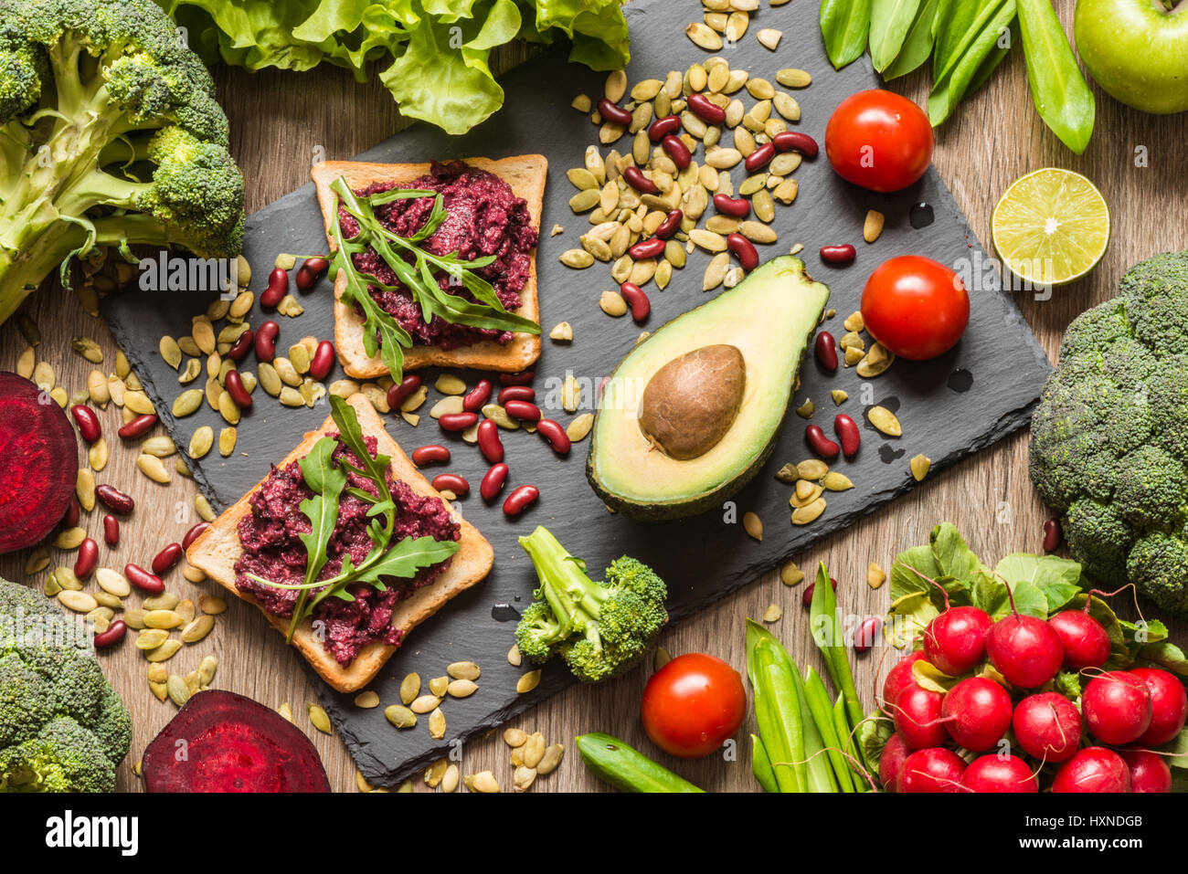Healthy vegan food. Sandwiches and fresh vegetables on wooden background. - Stock Image