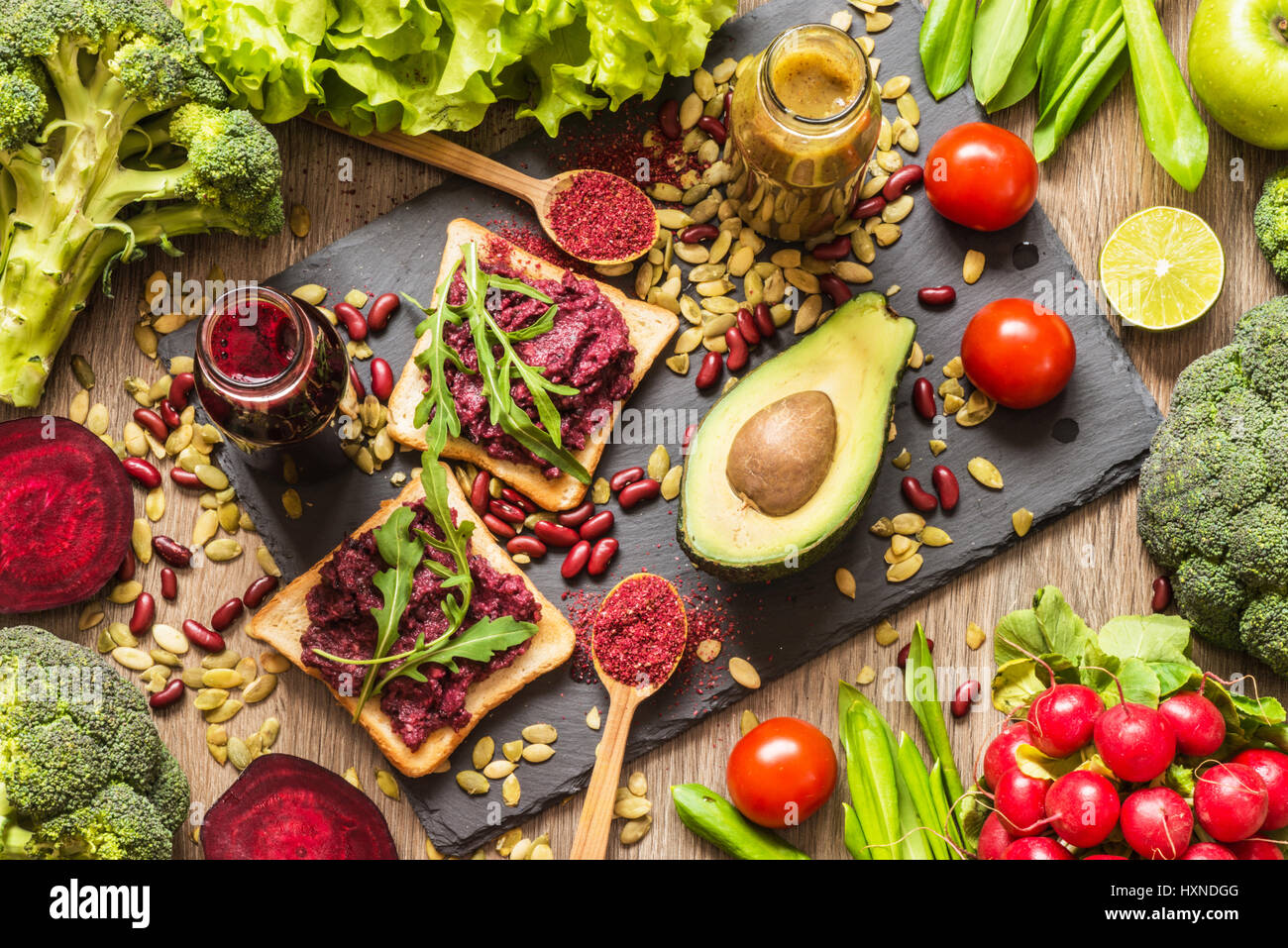 Healthy vegan food. Sandwiches and fresh vegetables on wooden background. Detox diet. Different colorful fresh juices - Stock Image