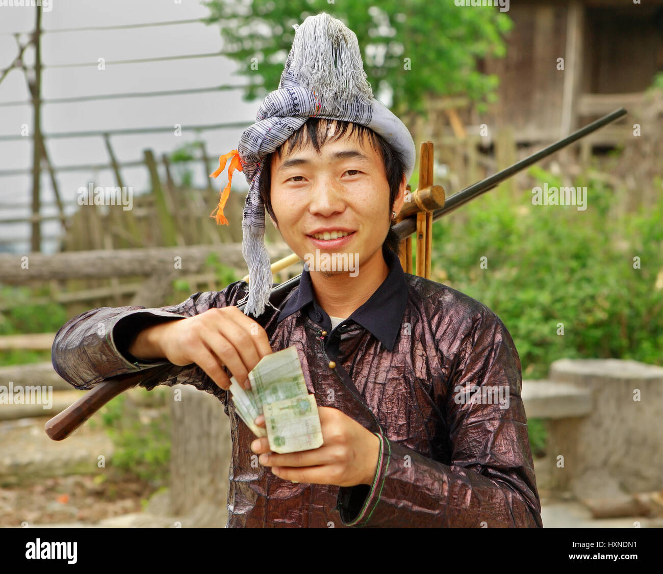 GUIZHOU PROVINCE; CHINA - APRIL 10: Man Miao ethnic group, with a musket on his shoulder, counts Yuan earned at - Stock Image
