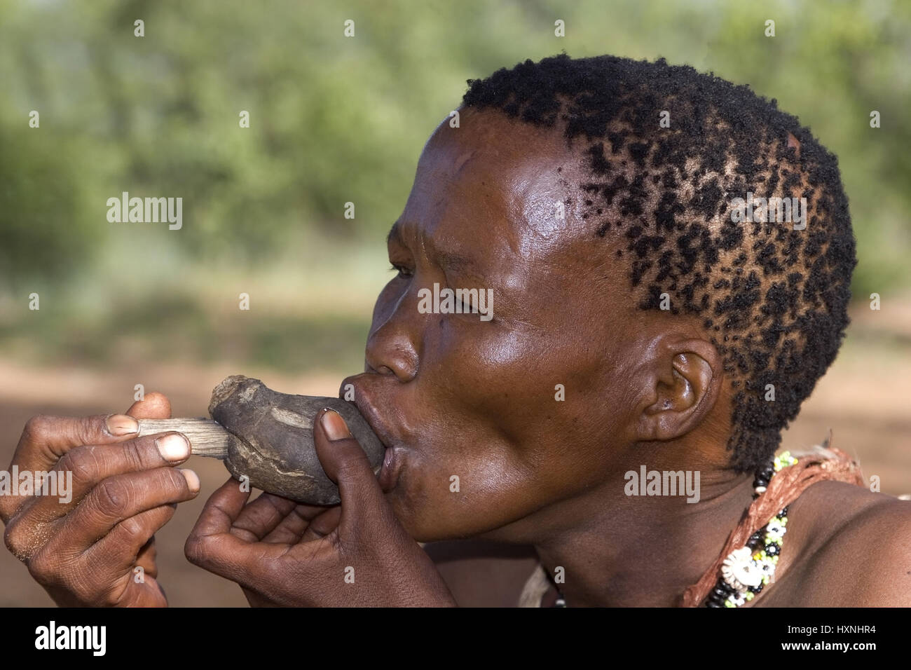 Bushman woman smokes a primitve whistle. Namibia, Buschmann  Frau raucht eine primitve Pfeife . Namibia - Stock Image