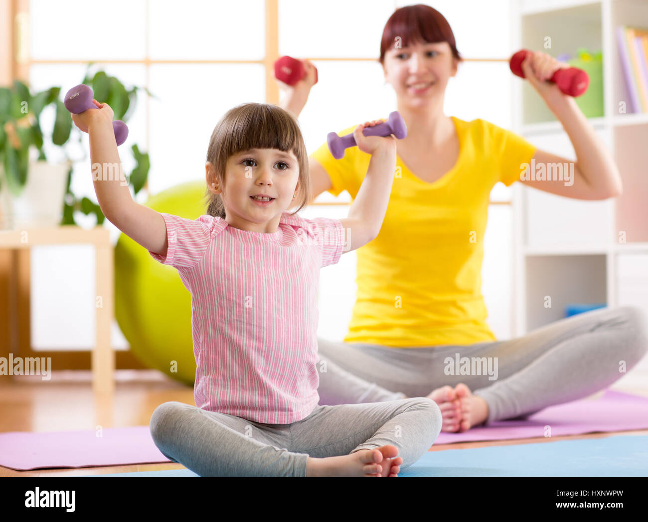 Woman and her child daughter doing fitness exercises with dumbbells - Stock Image