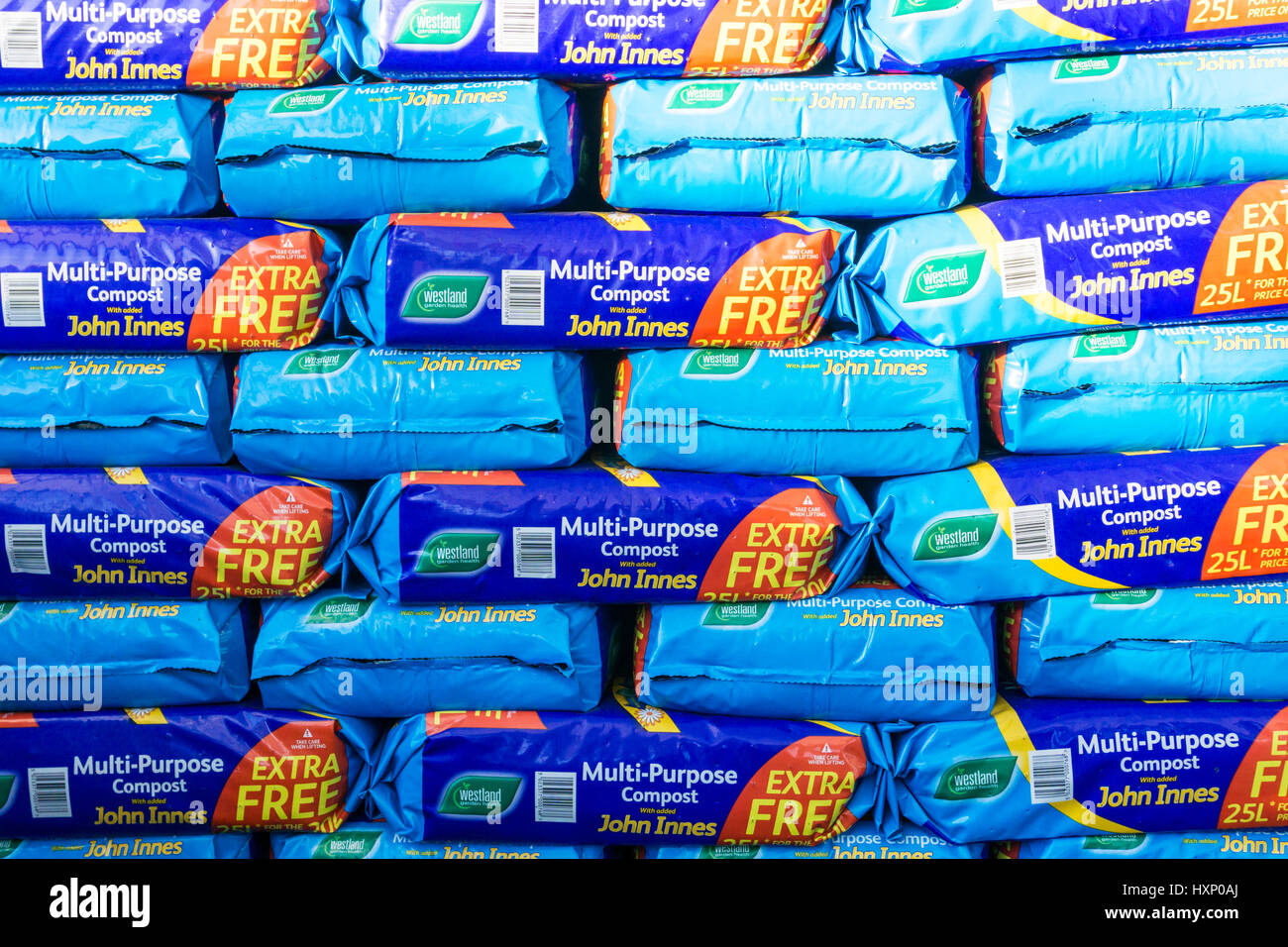 A stack of John Innes Multi-Purpose Compost bags for sale in a garden centre. - Stock Image