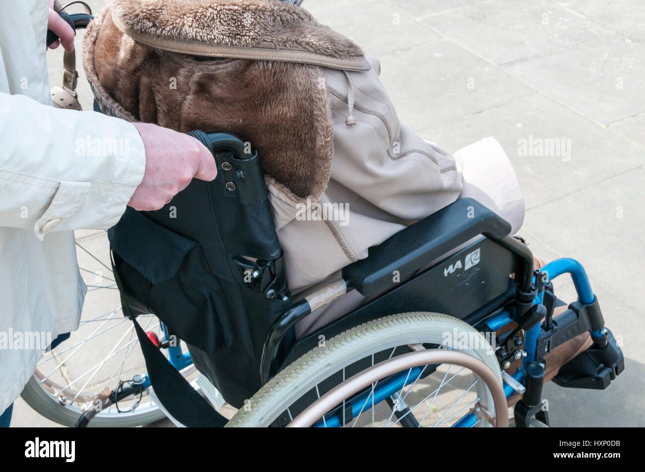 Elderly lady in wheelchair being pushed by carer. - Stock Image