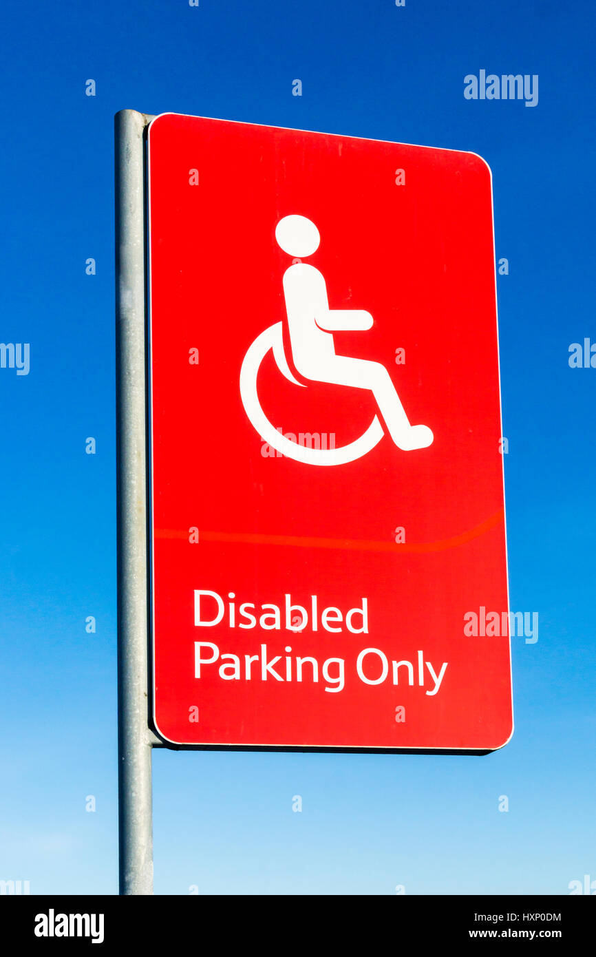 A red Disabled Parking Only sign against a clear blue sky. - Stock Image