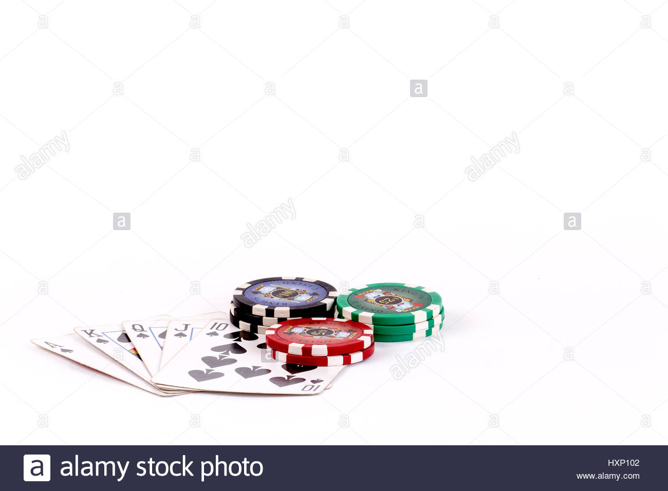 Overhead closeup of a group of 5 playing cards making up a spade royal flush hand with gambling chips set on them - Stock Image