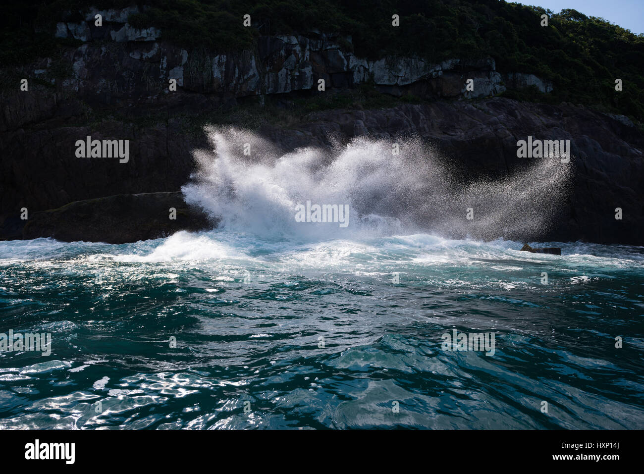 A wave crashes on the rocky cliffs of Ilhabela Stock Photo