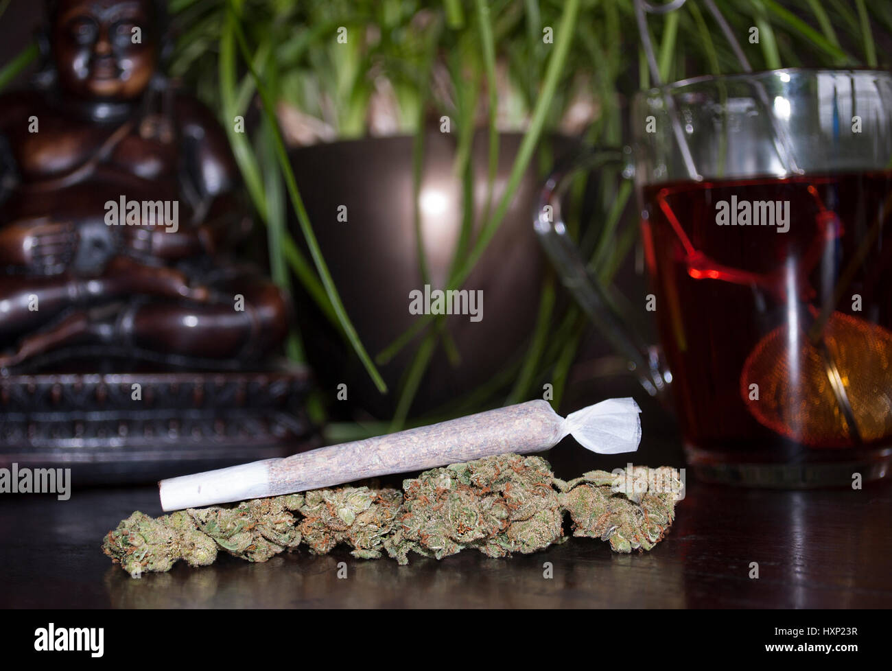 closeup of rolled marijuana weed joint and buds on wooden background, with Buddha statuette and cup of rooibos tea Stock Photo