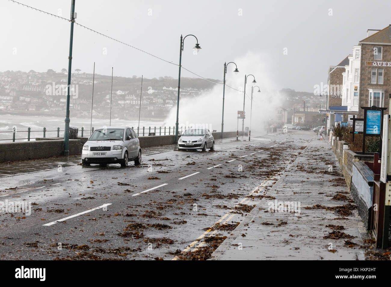 waves breaking over the seafront in Penzance during a winter storm - Stock Image