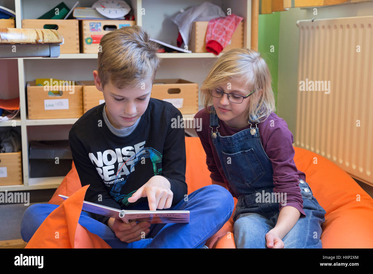 a boy and a girl reading a book together at primary school - Stock Image