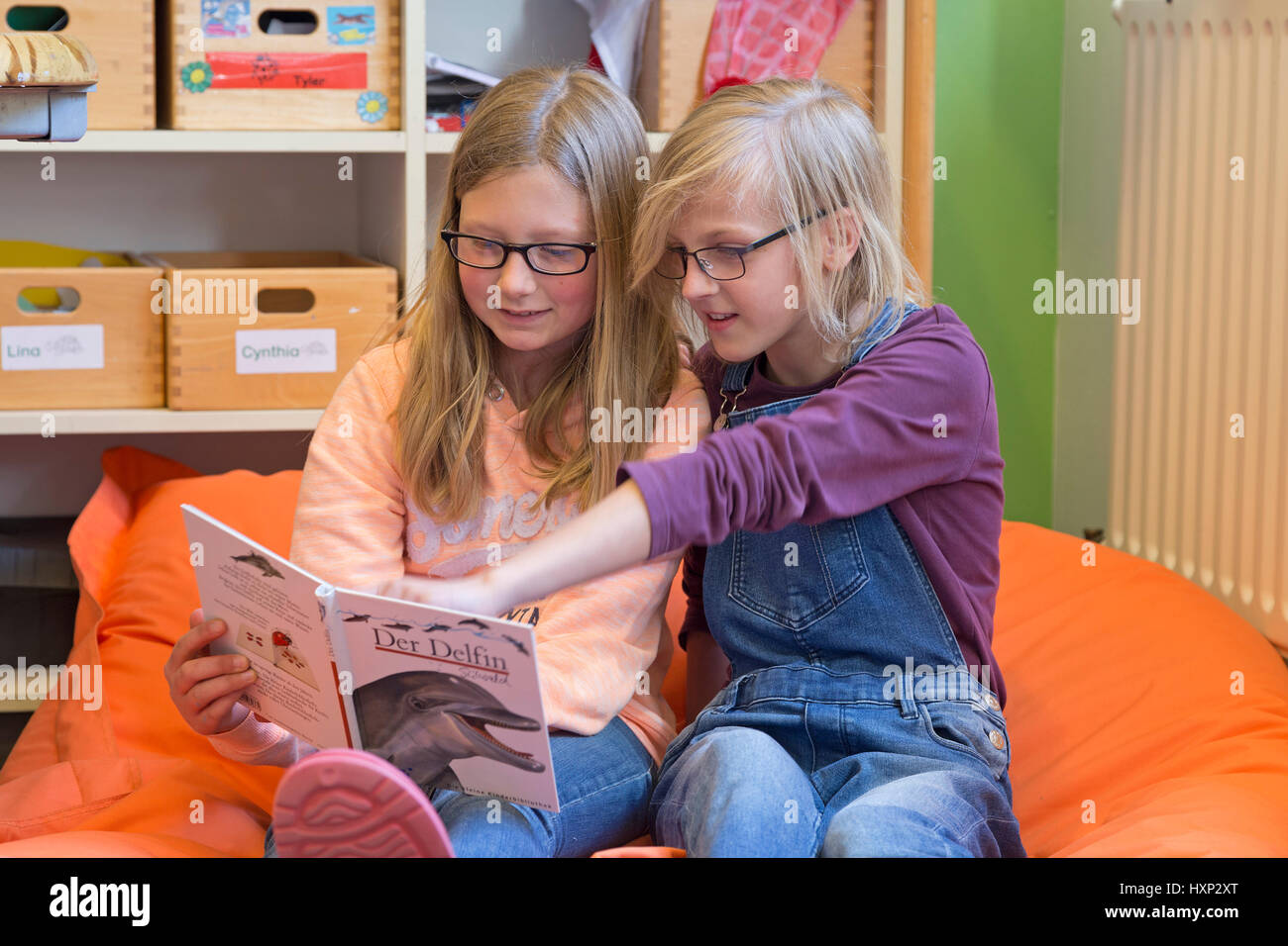 two girls reading a book together at primary school - Stock Image
