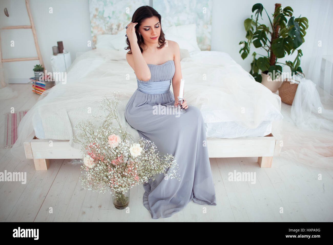 Cute girl with makeup in a blue evening dress sitting on the bed. In ...