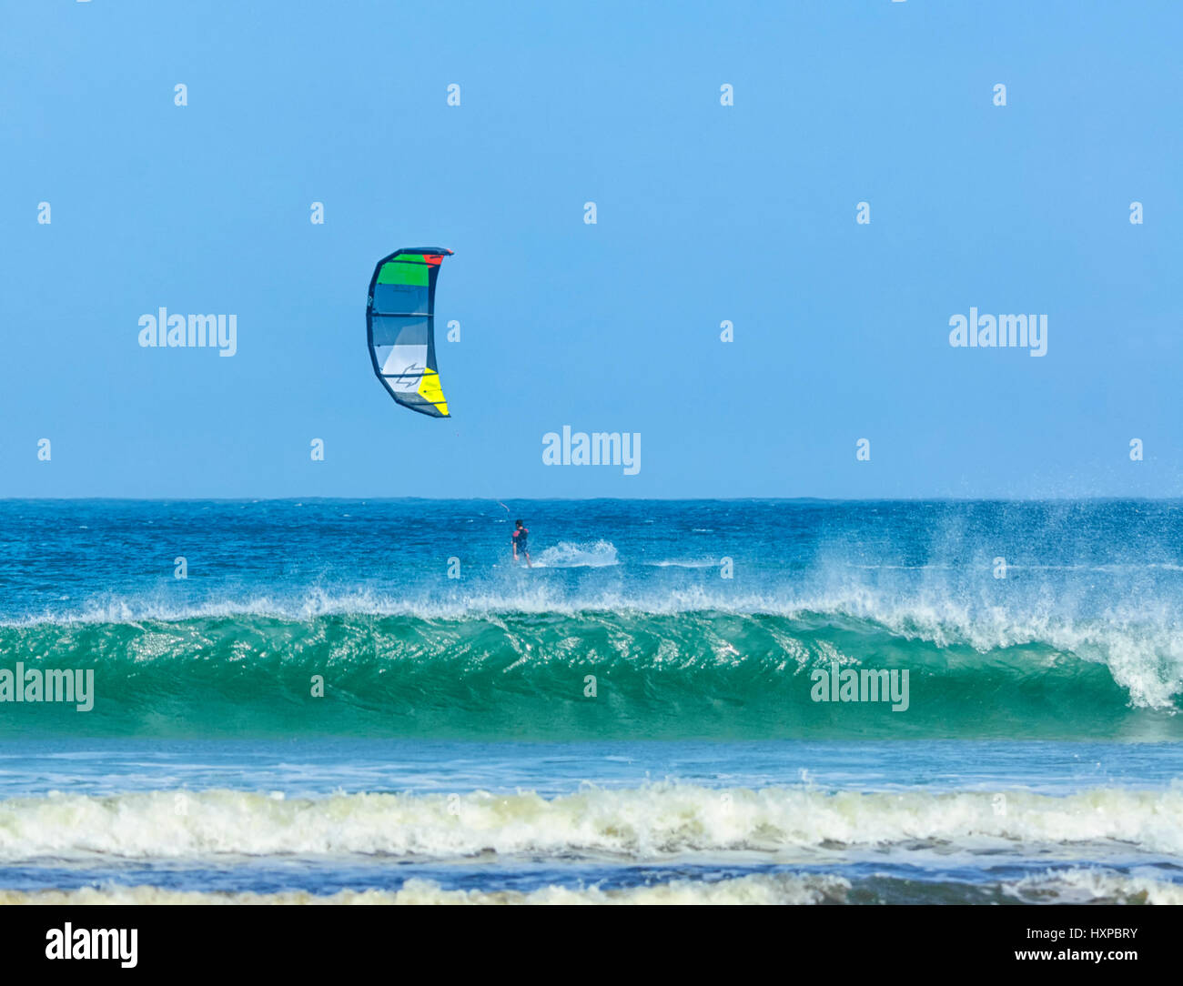 Kite surfer with a turquoise breaking wave at Seven Mile Beach, Gerroa, Illawarra Coast, New South Wales, NSW, Australia - Stock Image