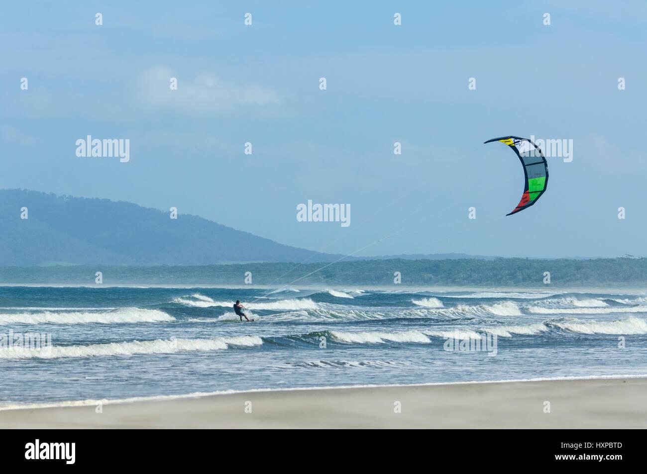 Kite surfer surfing among large waves at Seven Mile Beach, Gerroa, Illawarra Coast, New South Wales, NSW, Australia - Stock Image