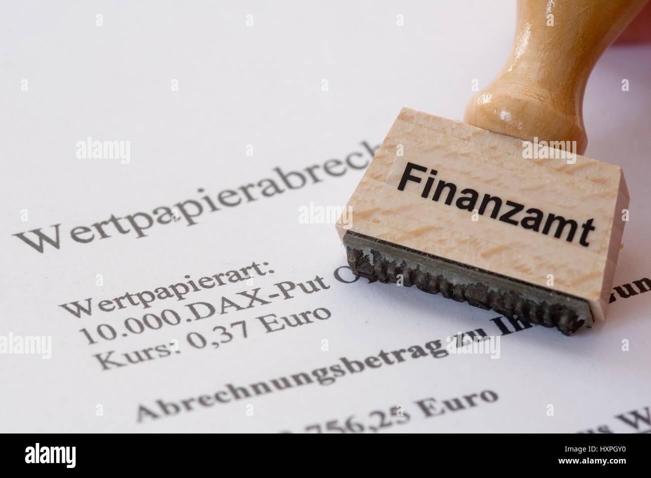 Stamp with label Tax office lies on security account, Stempel mit Aufschrift Finanzamt liegt auf Wertpapierabrechnung Stock Photo