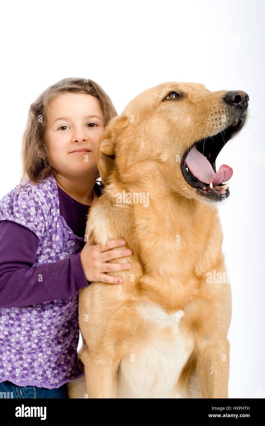 6-year-old girl cuddles retriever's schnauzer hybrid, sechsjähriges Mädchen schmust mit Retriever - Stock Image