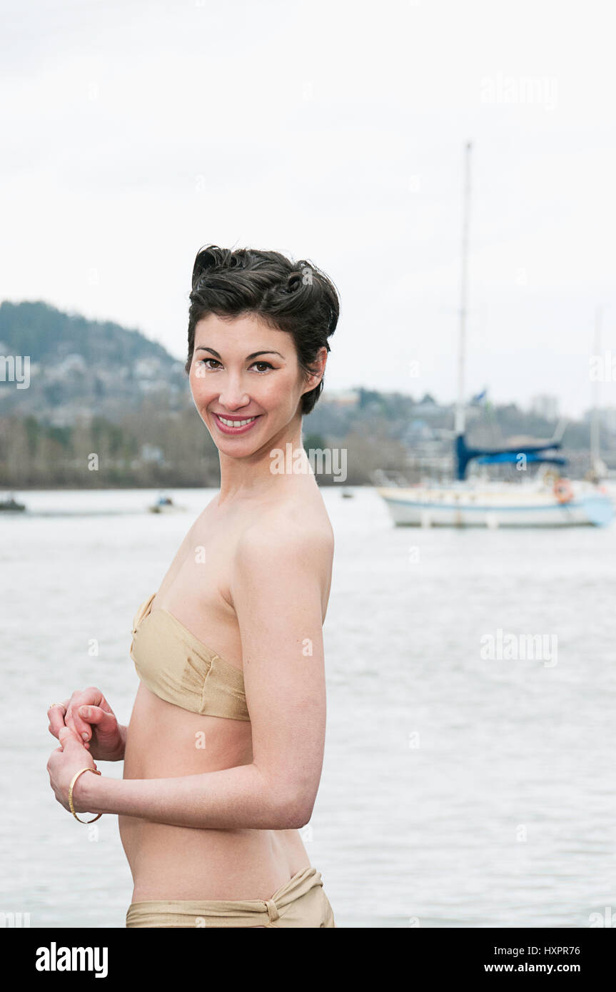 A woman in a bathing suit with a boat in the background photographed in Portland, Oregon. - Stock Image