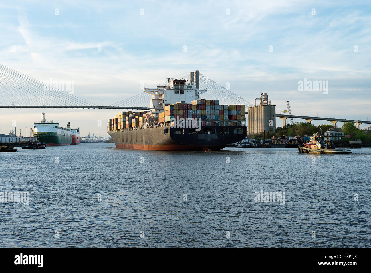 A container ship in Savannah Georgia with the Talmadge bridge in the background. - Stock Image