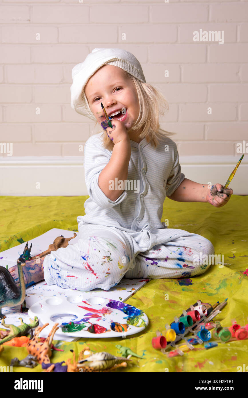 Happy little girl having messy play and  looking at the camera whilst painting. Childhood fun. - Stock Image