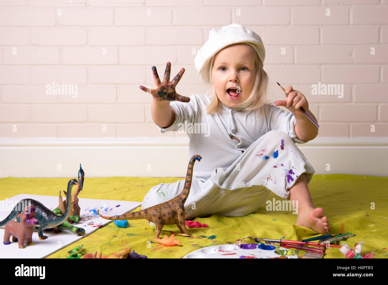 Little Girl having messy play with paints  and showing colorful painted hands. - Stock Image