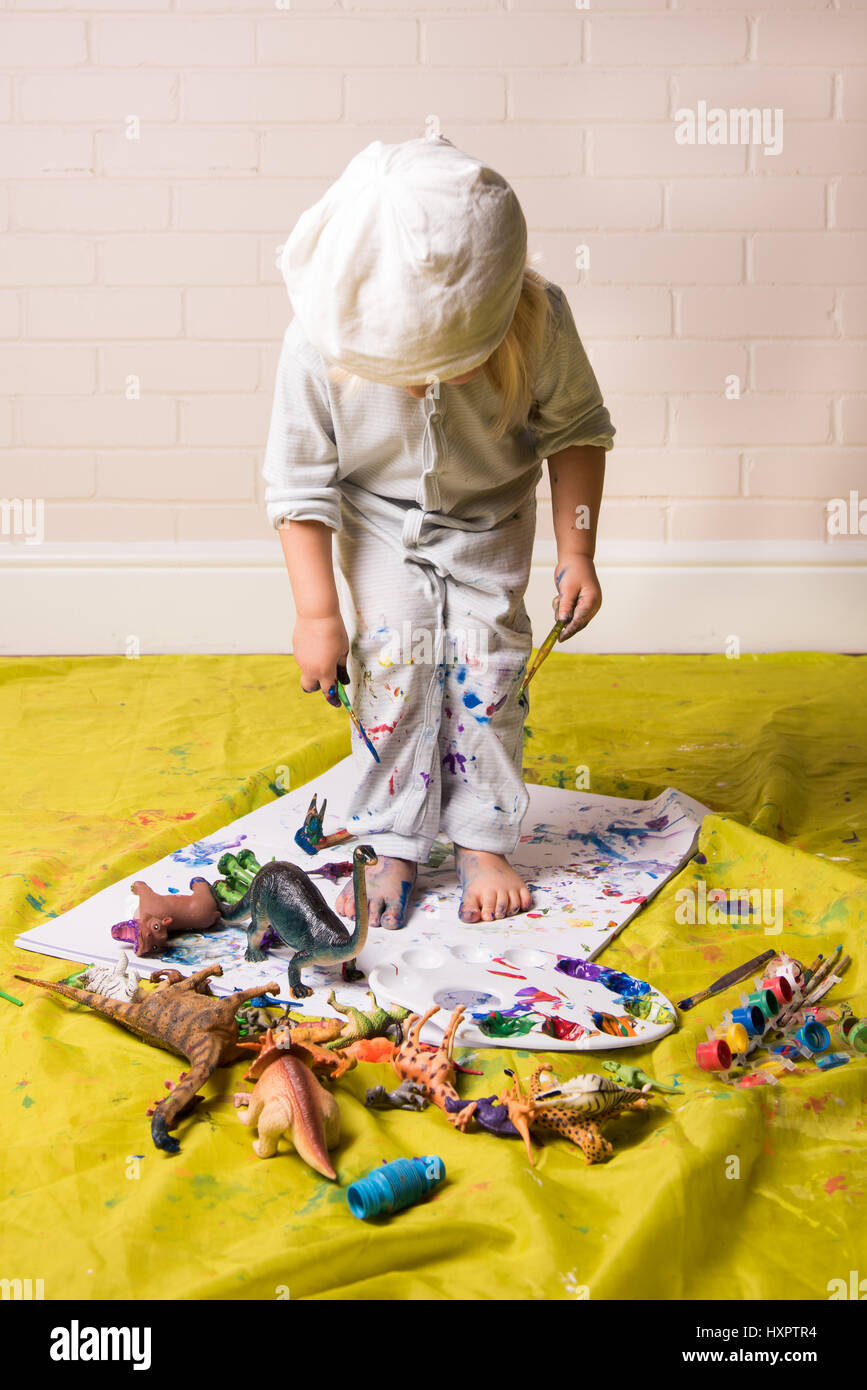 Child having messy play with paints and toys - Stock Image