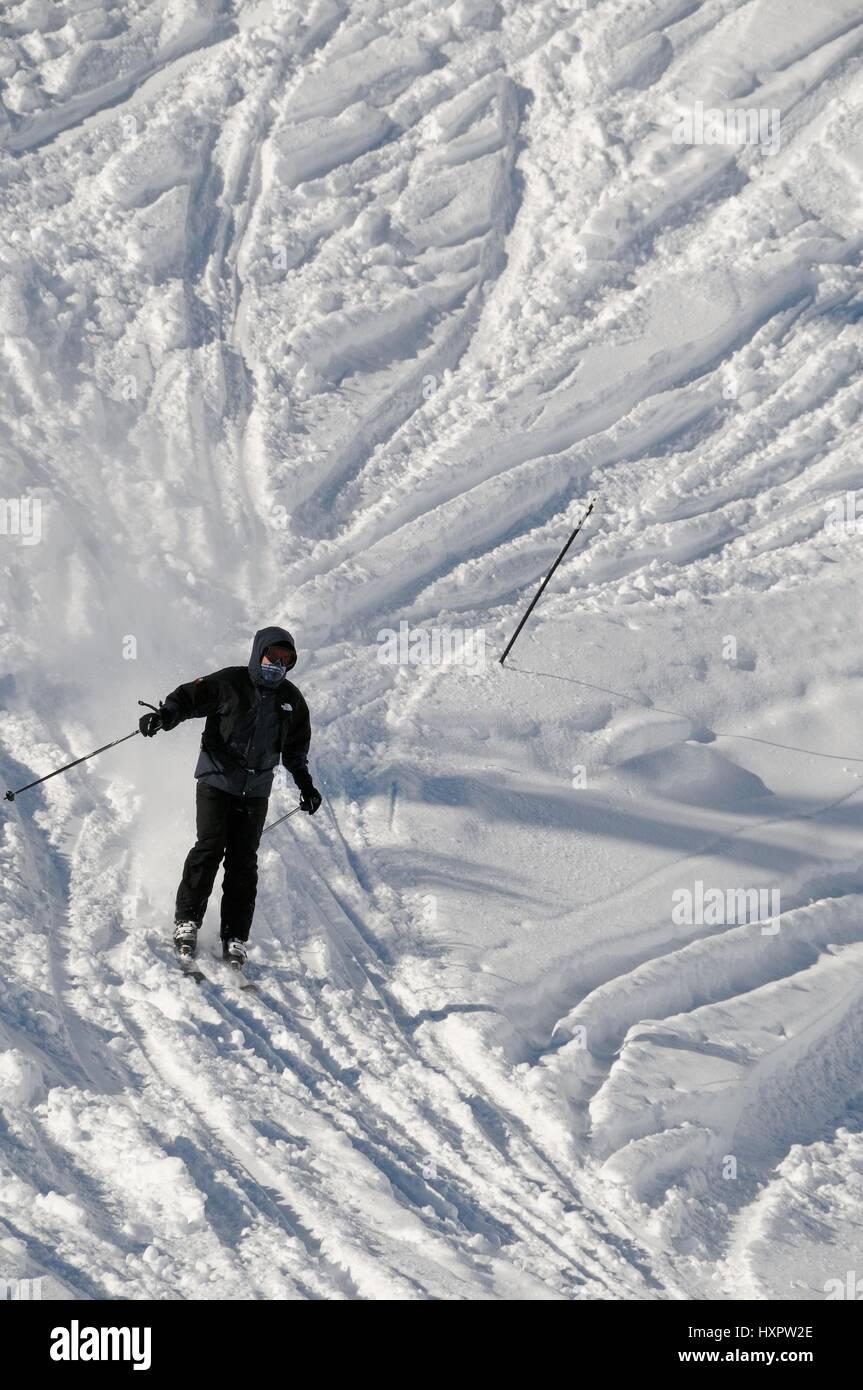 Skier descending a black piste at speed, Hauteluce / Les Contamines ski area, Savoie, France. - Stock Image
