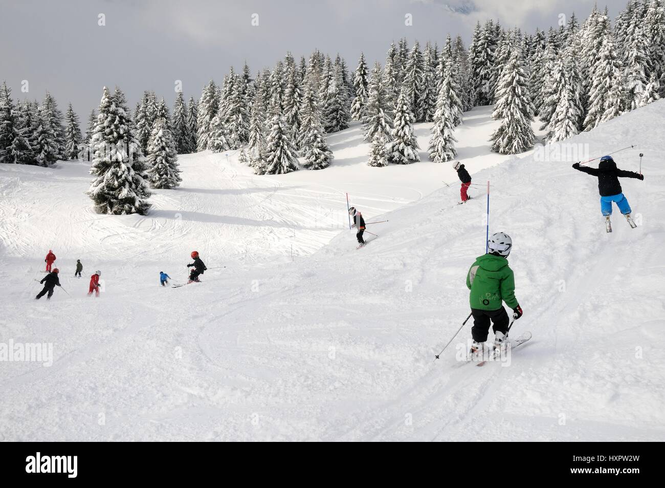 Ski school group of children following instructor down a piste, Les Houches, Savoie, France, February. - Stock Image