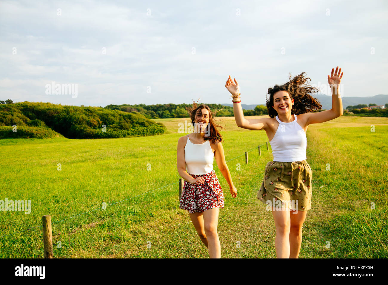 Funny female friends jumping in a green field - Stock Image