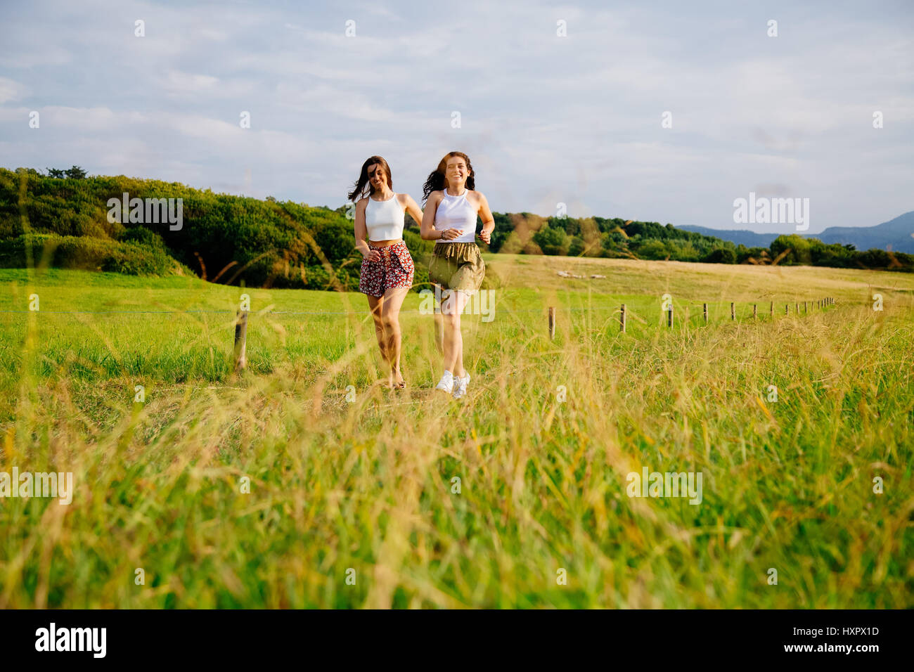 Funny female friends running in a meadow in summer - Stock Image
