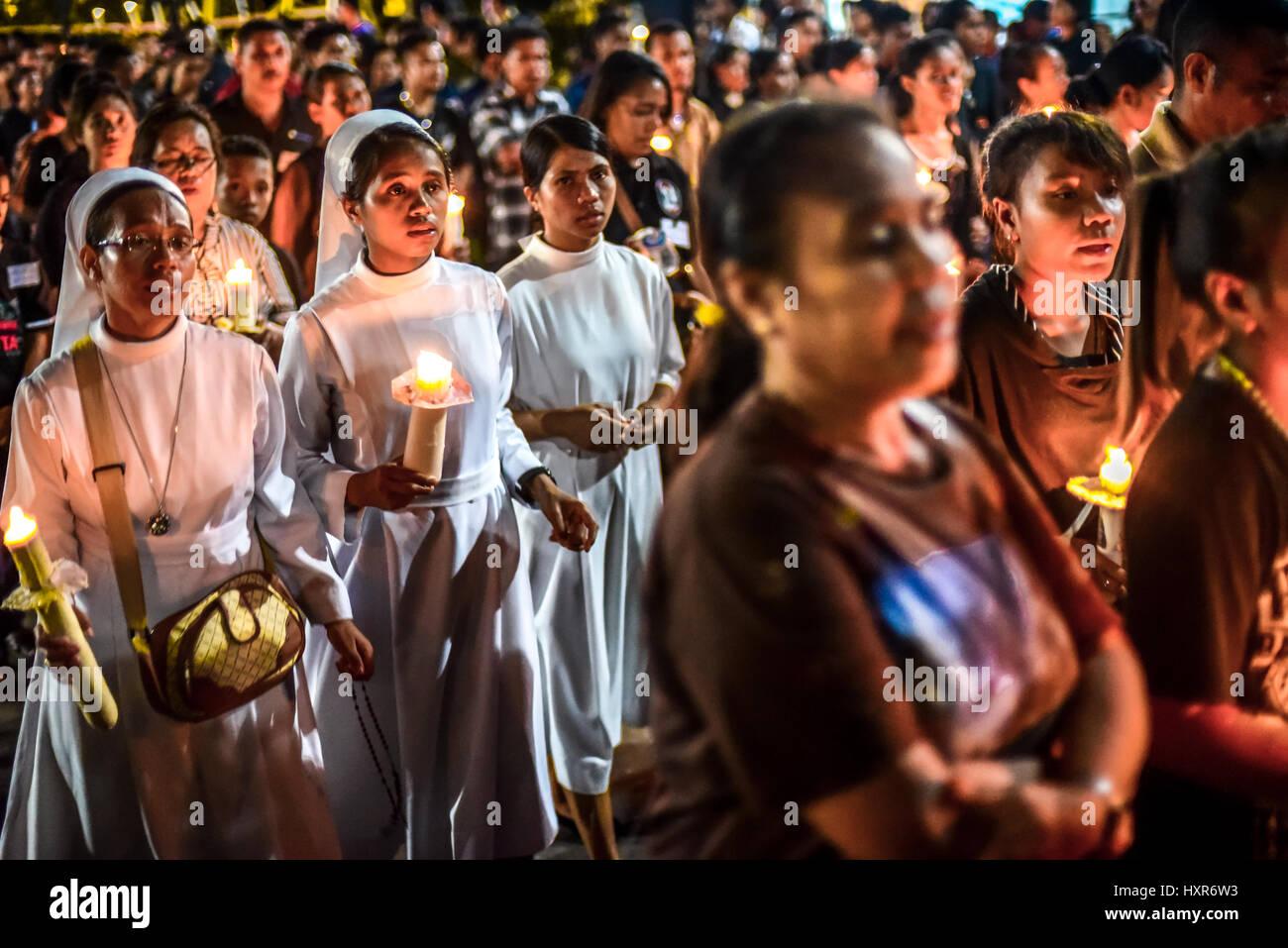 Roman Catholic nuns march among the crowd during Semana Santa procession as a part of Holy Week celebration in Larantuka, - Stock Image