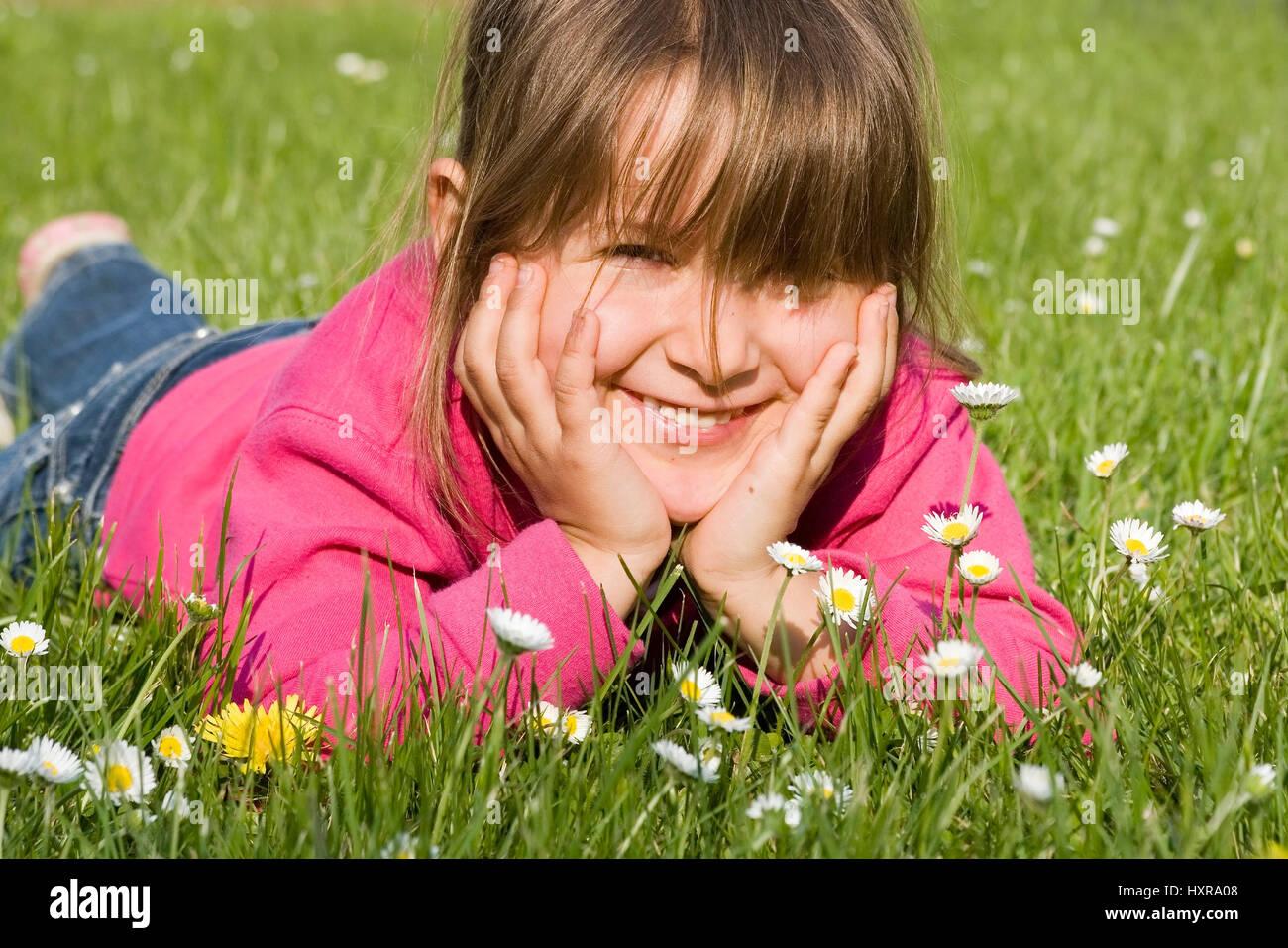 four-year-old girl lies laughing in the grass (mr), vierjähriges Mädchen liegt lachend im Gras (mr) Stock Photo