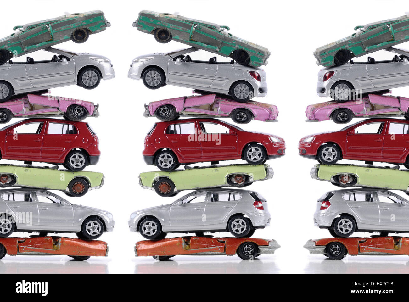 Broken and new stacked miniature cars, stagnant new carriage sales at the end of the cash for clunkers, Kaputte und neue gestapelte Miniaturautos, sto Stock Photo