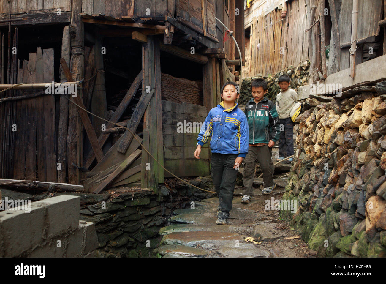 Xiaozhai village, Guangsi province,China - April 5, 2010: Rural schoolboys teenagers, 12 years old, walking down - Stock Image