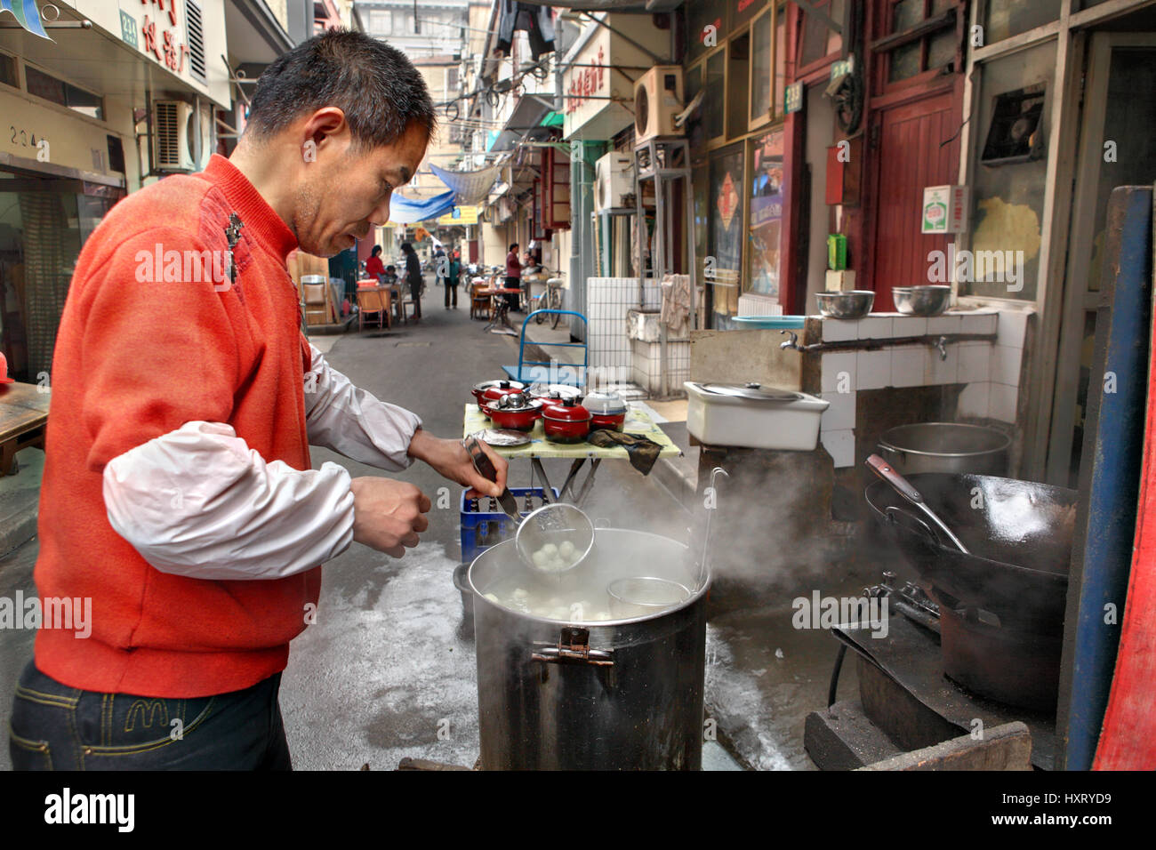 Shanghai, China - April 20, 2010: Seller street food, outdoor, cooking dumplings in a big pot - Stock Image