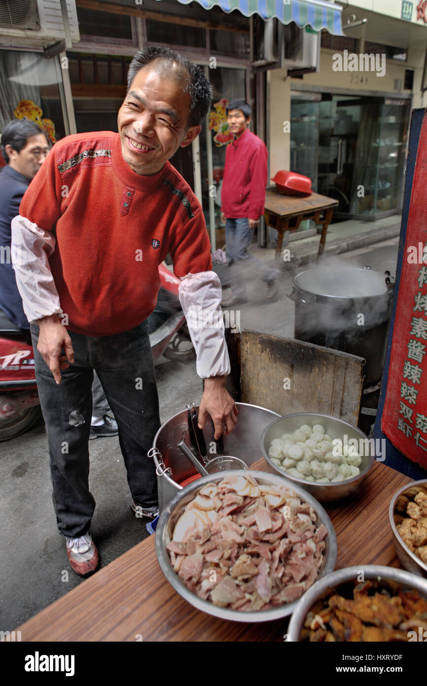 Shanghai, China - April 20, 2010: Outdoor affable chef prepares dishes trades in a narrow street. - Stock Image
